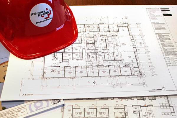 Primary Health construction hat on top of blueprints for the new Orchard Urgent Care Clinic