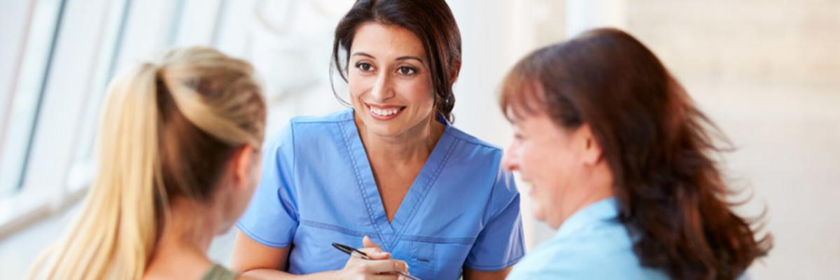 Young nurse or doctor talking with young woman and mature woman, career concept, interview concept