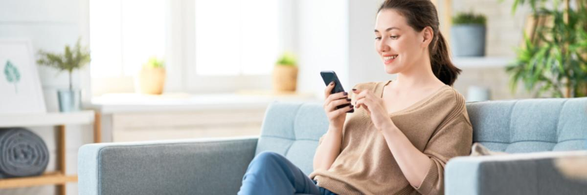 Young woman sitting on couch using cell phone, Telehealth Services